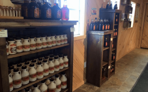 maple syrup bottles on wooden shelves   Top Local Destinations To Visit This Summer on The Dumfries Summer Trail
