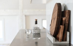 wood cutting board and glass bottle and water glass sitting on black counter, white background