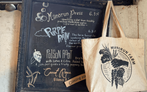 cream coloured reusable bag with manorun farm logo hanging beside a black chalk board   Top Local Destinations To Visit This Summer on The Dumfries Summer Trail