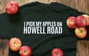 """Forrest green tshirt that reads """"I pick my apples on howell road"""" with apples laying around it.   Top Local Destinations To Visit This Summer on The Dumfries Summer Trail"""