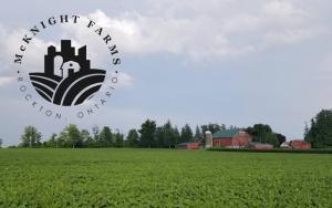 red farm off the distance, farm fields, McKnight farms logo in left corner
