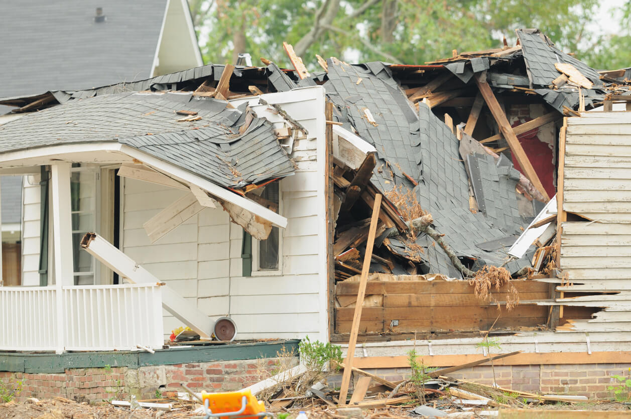 damaged home with collapsed roof